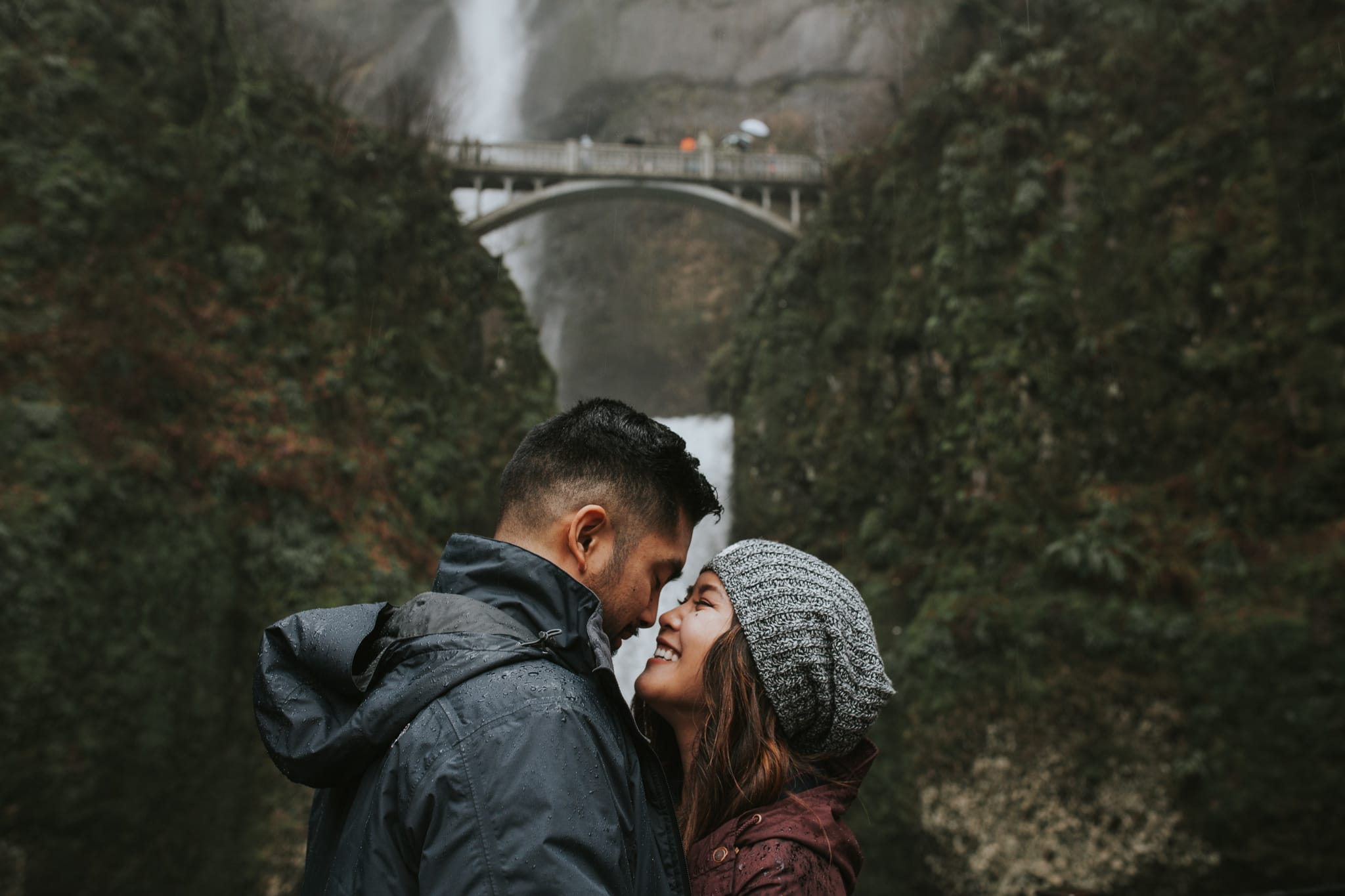 cute couple smiling in front of Multnomah Falls by Marcela Pulido Portland Wedding Photographer