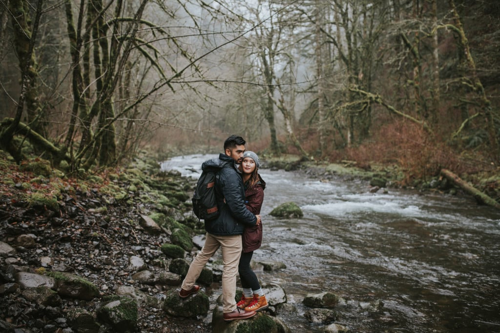 couple hiking by river wahclella falls by Marcela Pulido Portland Wedding Photographer