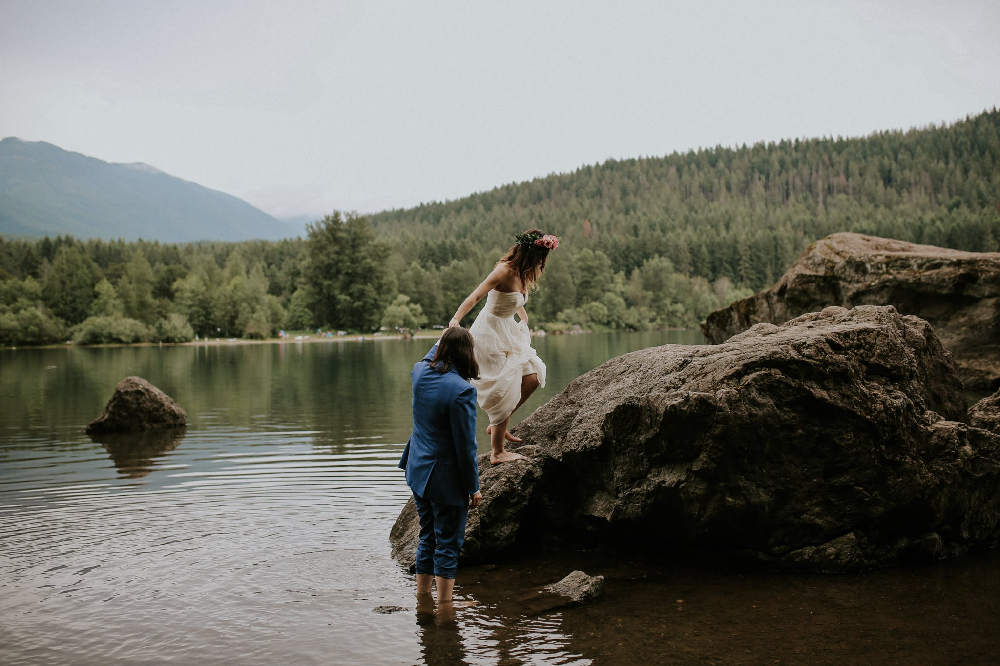 bride walks on rock groom helps Rattlesnake Lake Wedding Marcela Pulido Photography