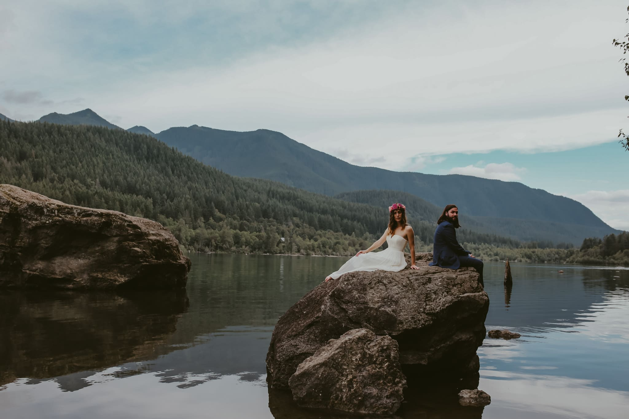 bride and groom on rock on water Rattlesnake Lake Wedding Marcela Pulido Photography
