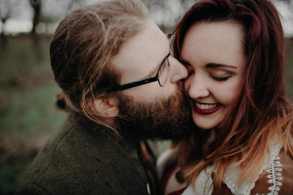 guy kisses girl on cheek Powell Butte Portland Engagement Photographer by Marcela Pulido Photography Portland Wedding Photographer