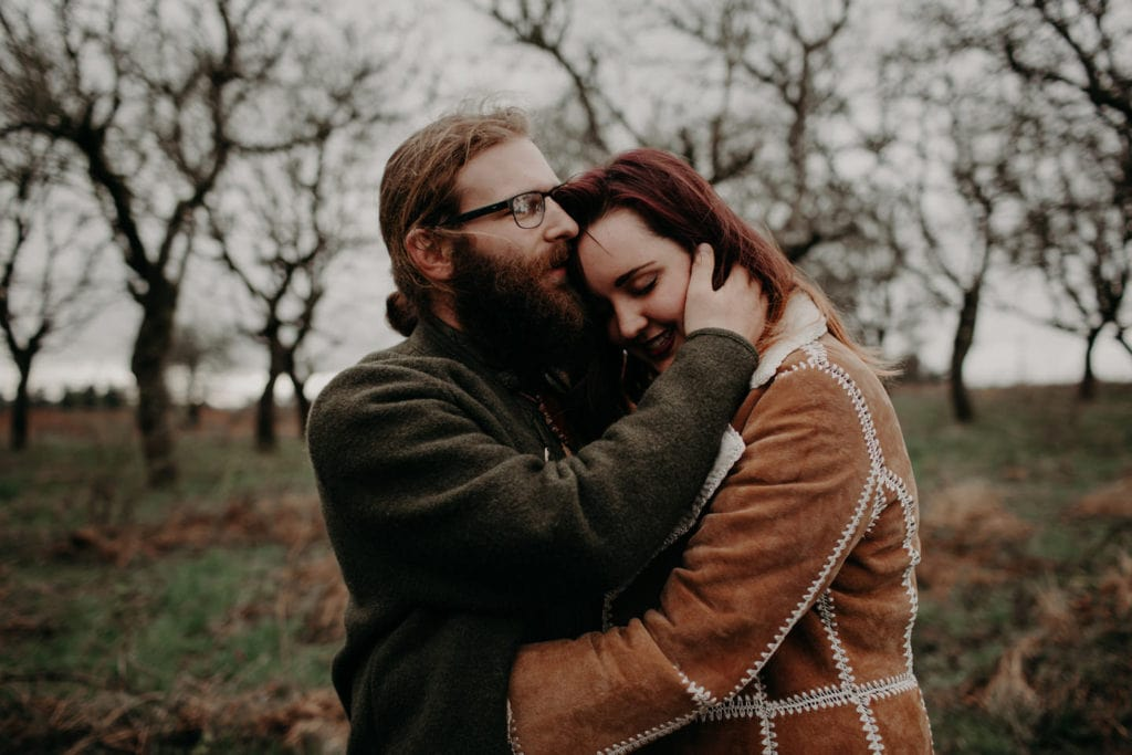 cute boho hippie couple embrace in forest Powell Butte Portland Engagement Photographer by Marcela Pulido Photography Portland Wedding Photographer