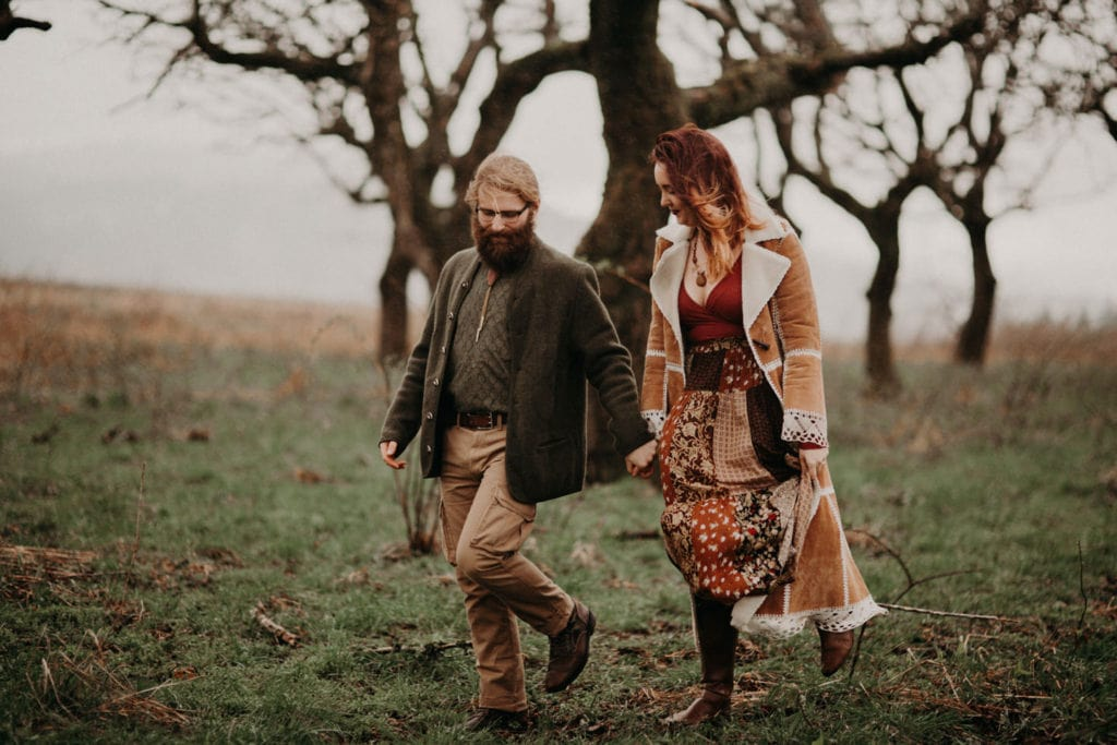 cute hippie boho couple walk hand in hand in forest Powell Butte Portland Engagement Photographer by Marcela Pulido Photography Portland Wedding Photographer