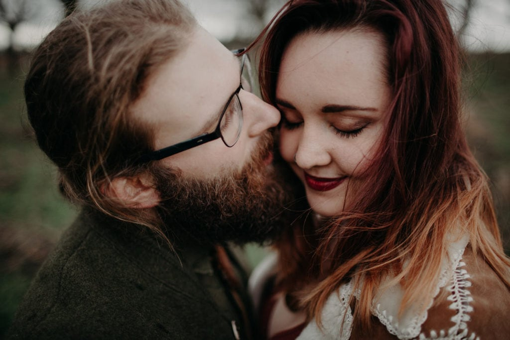 man kisses fiance on cheek close up Powell Butte Portland Engagement Photographer by Marcela Pulido Photography Portland Wedding Photographer