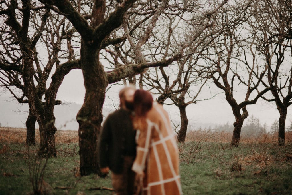 couple out of focus forest in focus Powell Butte Portland Engagement Photographer by Marcela Pulido Photography Portland Wedding Photographer
