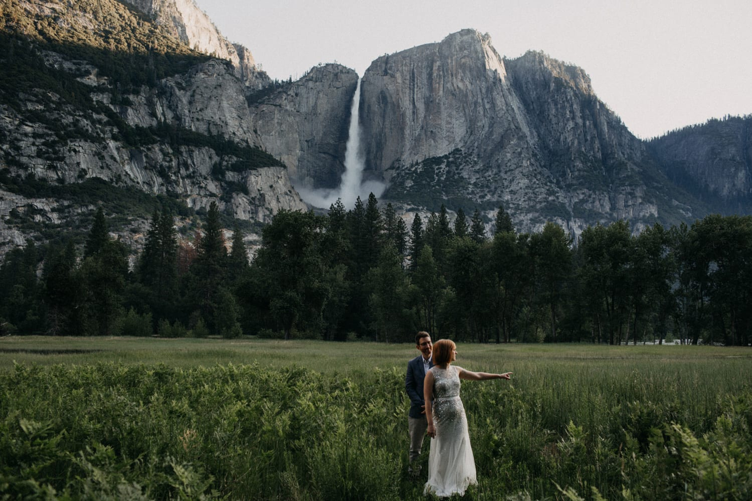 Anjali and Ben in a meadow in front of Yosemite Falls for their elopement