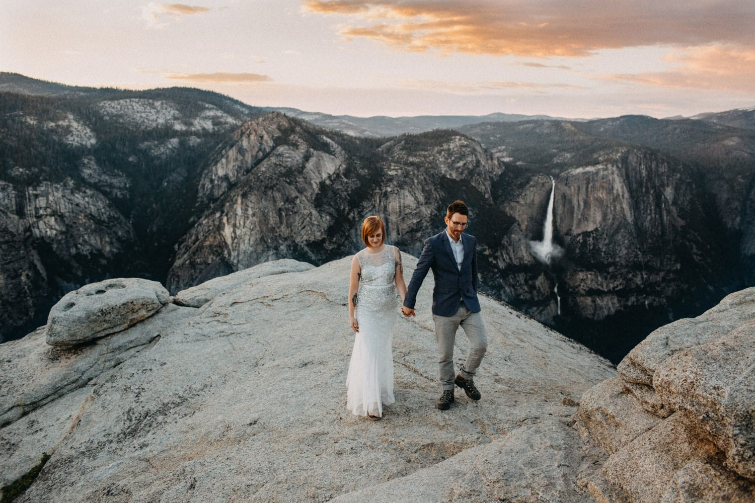Anjali and Ben atop Taft Point at sunset for their Yosemite Elopement with Upper Yosemite Falls in the background