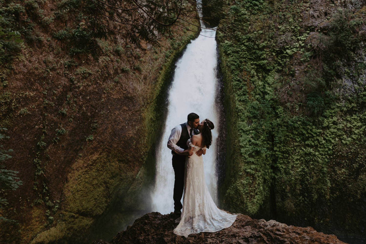 newlywed couple kissing in front of Wahclella Falls Columbia River Gorge elopement