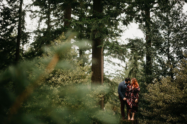 through the trees shot of Francisco and Samantha snuggling up at Hoyt Arboretum in Washington Park engagement